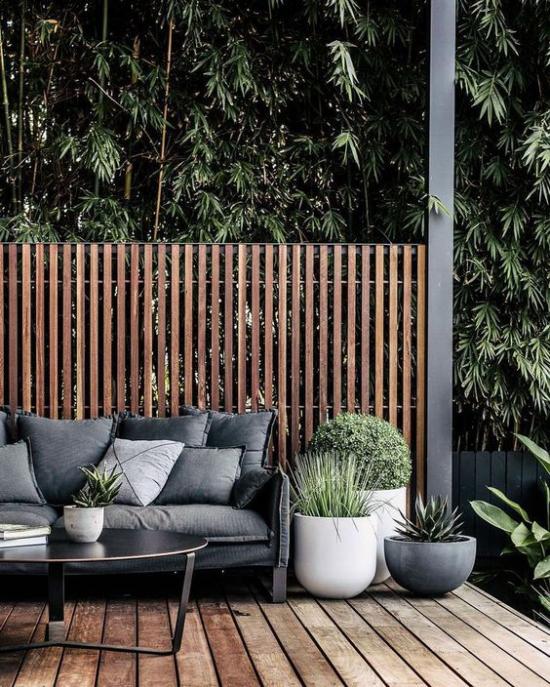Holzterrasse gestalten bequeme Möbel Sichtschutz Pflanzgefäße