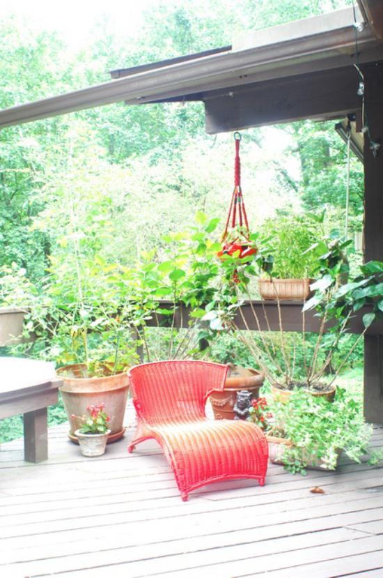 Holzterrasse gestalten einfach bequem roter Liegestuhl viel Grün ringsum