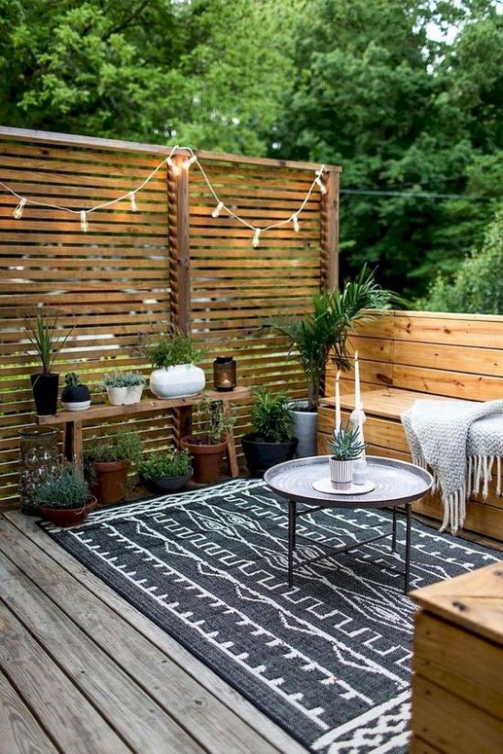Holzterrasse gestalten einfach rustikal bunter Teppich Lichterkette an der Holzwand