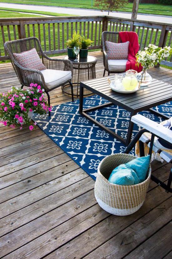 Holzterrasse gestalten graue Holzdielen blauer Teppich bequeme Möbel Pflanzen Blumen
