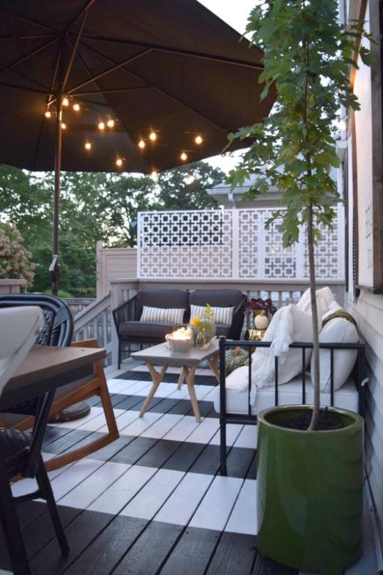 Holzterrasse gestalten großer schwarzer Sonnenschirm Lichterkette bequeme Möbel grüne Pflanze