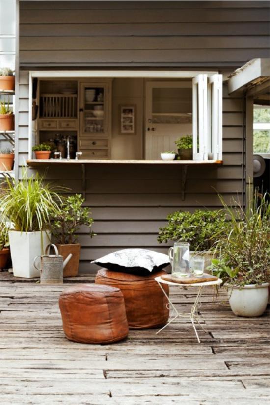 Holzterrasse gestalten großes Fenster zur Küche Lederhocker viele grüne Pflanzen