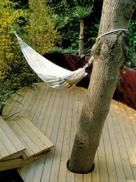 Holzterrasse gestalten hoher Baum Hängematte für puren Relax