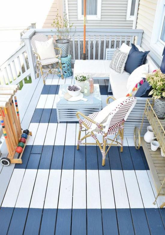 Holzterrasse gestalten mediterranes Flair weiß blau dominierende Farben Deko Kissen