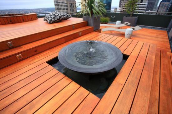 Holzterrasse gestalten minimalistisch Feuerschale Liegestühle