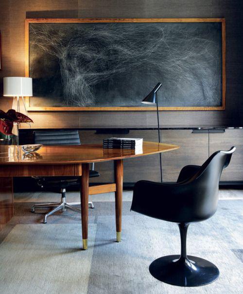 Maskulines Homeoffice großer Tisch schwarzer Sessel Lampen dunkles Wandbild