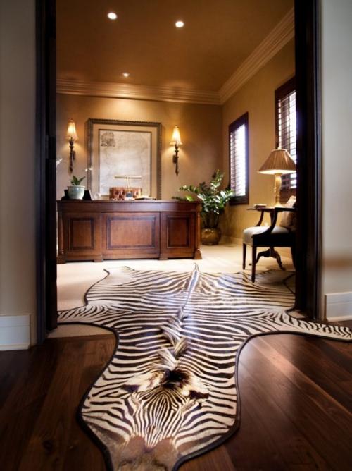 Maskulines Homeoffice luxuriös großes Fell auf dem Boden Schreibtisch im Hintergrund gut durchdachte Beleuchtung Sessel