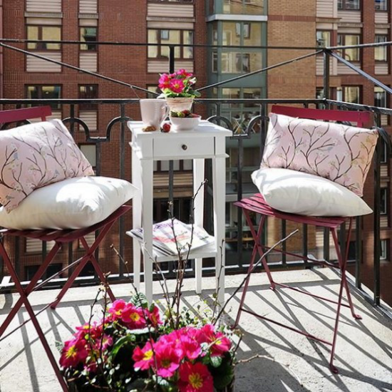 Sommerblumen Deko Ideen den Balkon dekorieren Blumen in Töpfen zwei Stühle hoher Tisch Kissen