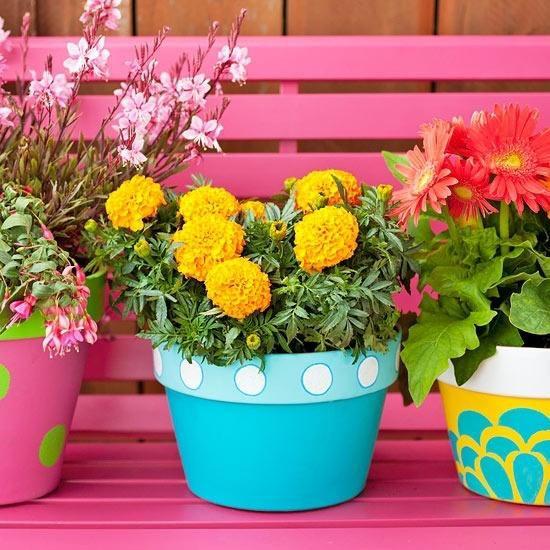 Sommerblumen Deko Ideen gelbe Tagetes schöne Gerbera bunte Töpfe auf der Sitzbank