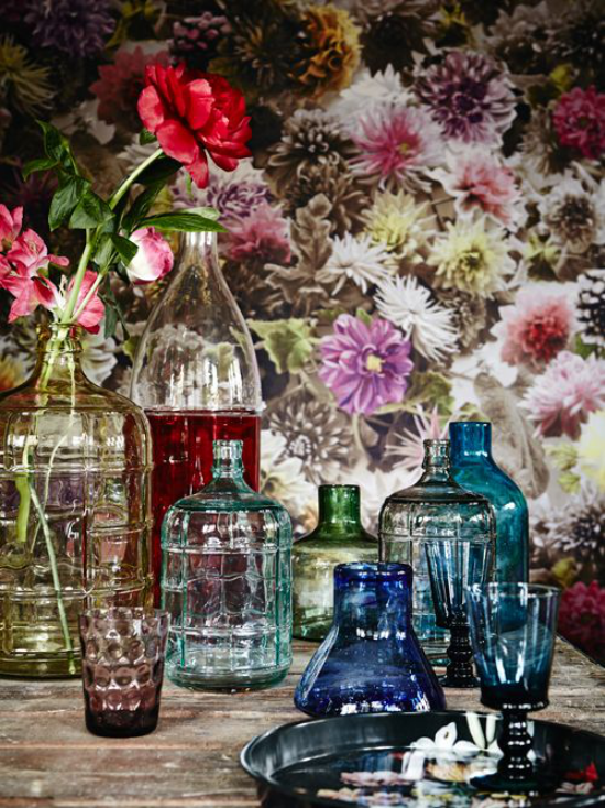 Sommerblumen Deko Ideen viele Vasen aus buntem Glas Blumen gemusterte Tapete