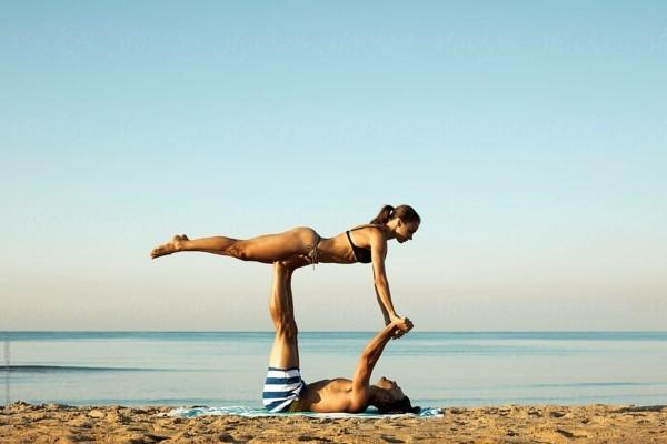 Yoga Übungen zu zweit Akro Yoga vordere Vogelhaltung Front Bird Pose am Strand