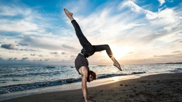 Yoga Sonnengruß Surya Namaskar am Strand beim Sonnenuntergang