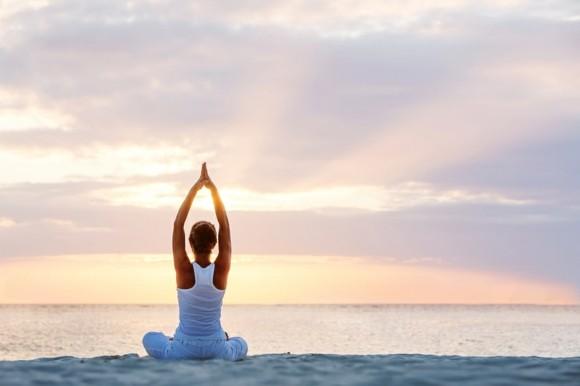 Yoga Sonnengruß am Strand beim Sonnenaufgang