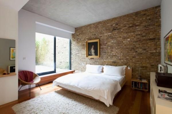 Backsteinwand im Schlafzimmer hinter dem Bett moderne weiße Einrichtung viel Tageslicht sehr ansprechende Atmosphäre