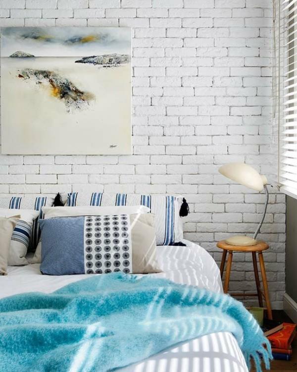 Backsteinwand im Schlafzimmer in Weiß gestrichen betont die ruhige Atmosphäre rustikales Flair Wandbild Hocker Nachtlampe
