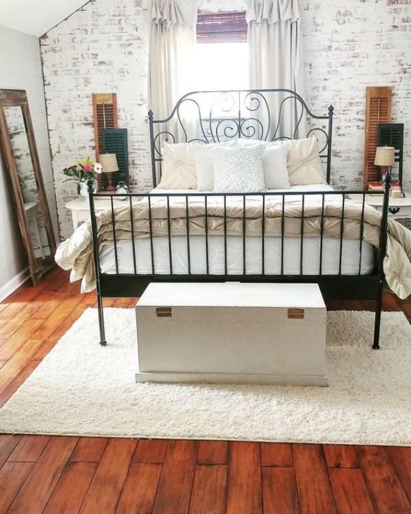 Backsteinwand im Schlafzimmer mit rustikalen Touches Metallbett Kommode angelehnter Spiegel