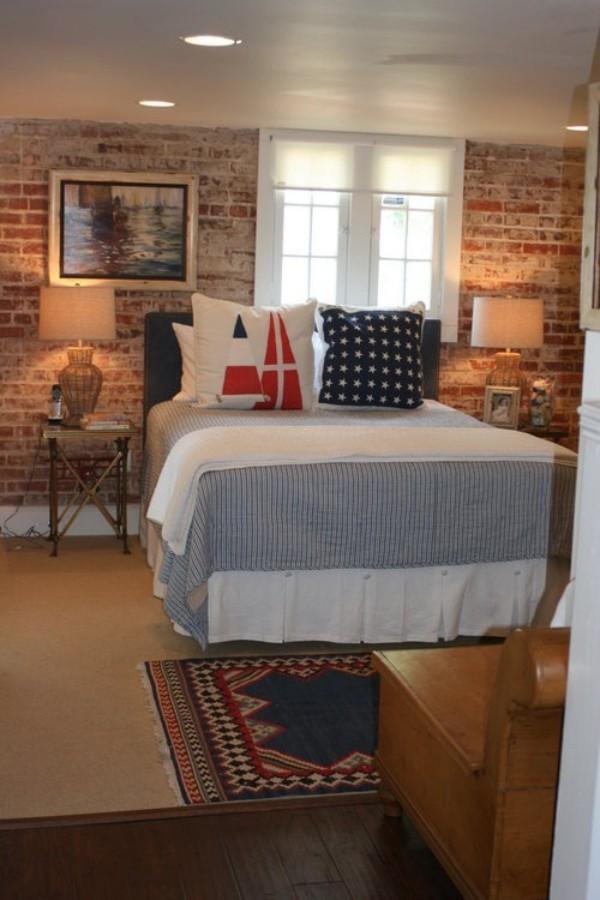 Backsteinwand im Schlafzimmer mit rustikalen Touches gute Beleuchtung hohes Bett Deko Kissen