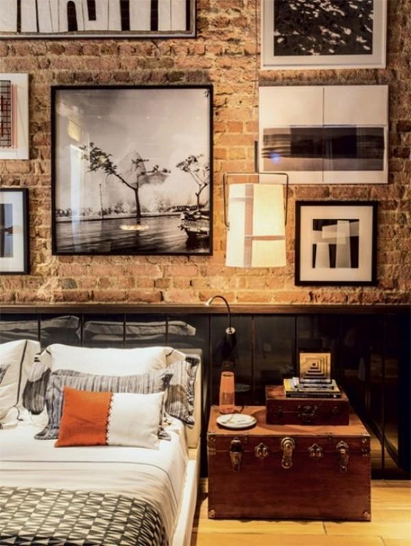 Backsteinwand im Schlafzimmer mit rustikalen Touches viele Bilder alter Koffer als Nachttisch
