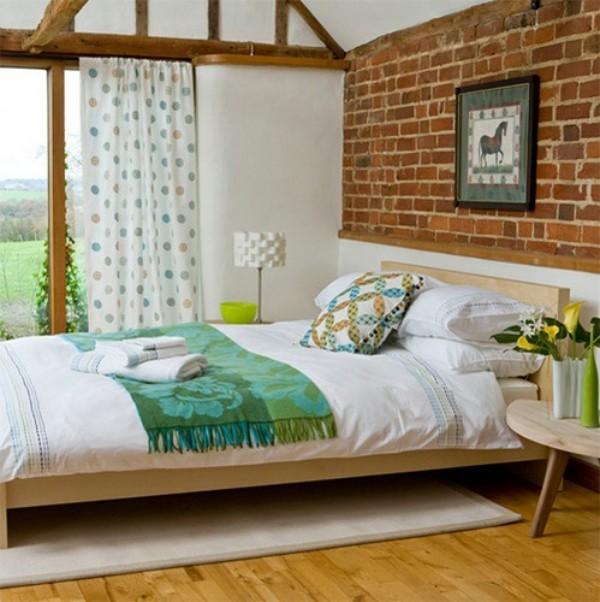 Backsteinwand im Schlafzimmer moderne Gestaltung helles Ambiente Holzbalken