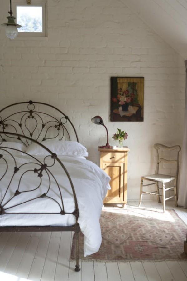Backsteinwand im Schlafzimmer moderne Gestaltung weiß dominiert Metallbett