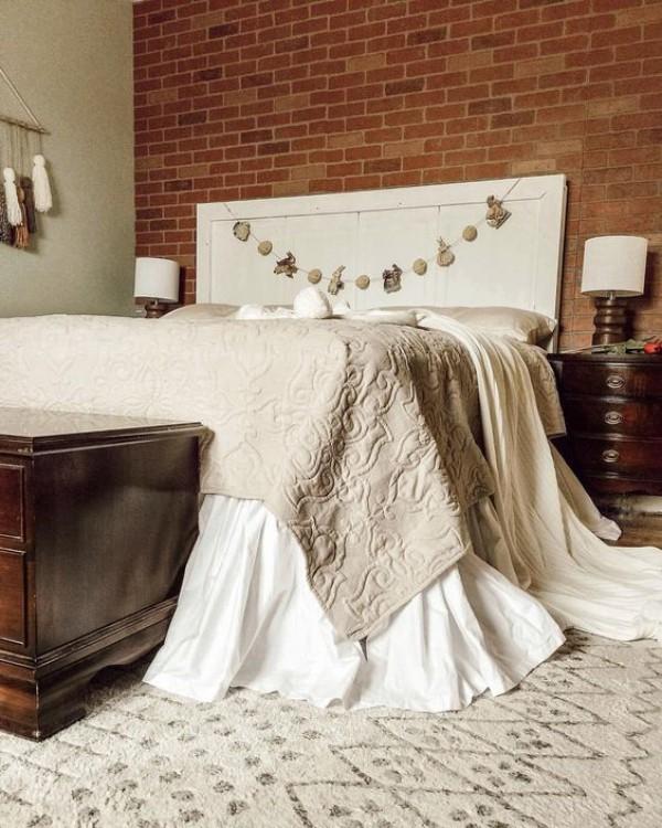 Backsteinwand im Schlafzimmer moderne Gestaltung weißes Bettkopfteil dunkelbraunes Holz weiß und grau