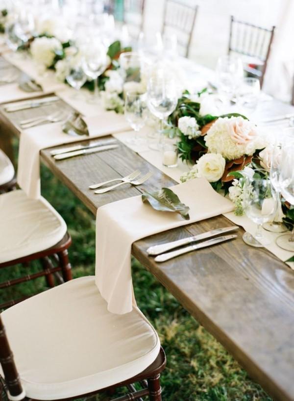 Hochzeitsdeko - weiße Servietten auf einem Holztisch