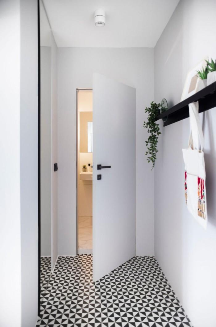 Kleines Apartment einrichten Flur ganz in weiß gestaltet kleine Akzente in Schwarz Regal
