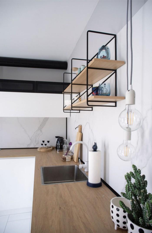 Kleines Apartment einrichten L-Form-Küche minimalistisch gestaltet weiße Wände offenes Regal Arbeitsplatten aus Holz Spüle Kakteen im Topf