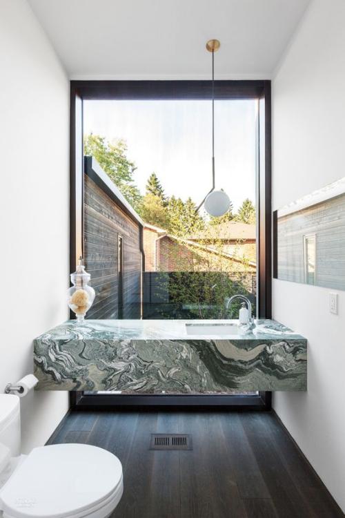Marmor im Bad Marmorfliesen großes Fenster smaragdgrüne Wanne weiße Badmöbel luxuriöses Design