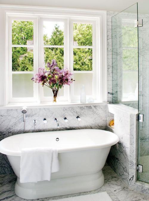 Marmor im Bad Marmorfliesen weiße Badewanne vor dem Fenster Vase mit Blumen feminines Flair