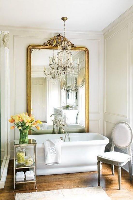 Pariser Chic im Bad moderne Badewanne großer Wandspiegel verzierter Rahmen Beistelltisch Blumen Kronleuchter Stuhl