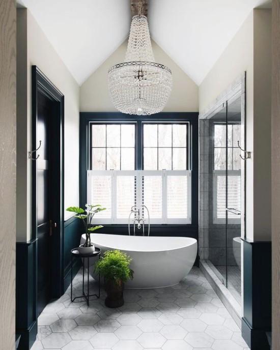 Pariser Chic im Bad moderne Badewanne ovale Form schickes Raumdesign zwei Grünpflanzen als Akzent großes Fenster Kristall-Kronleuchter