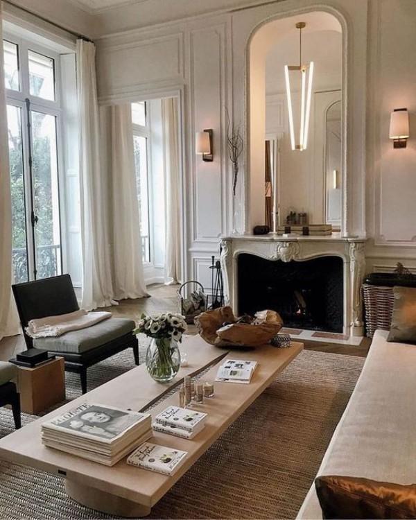 Pariser Chic im Wohnzimmer ansprechende Atmosphäre Spiegel über dem Kamin großes Fenster viel Licht Bücher auf dem Kaffeetisch
