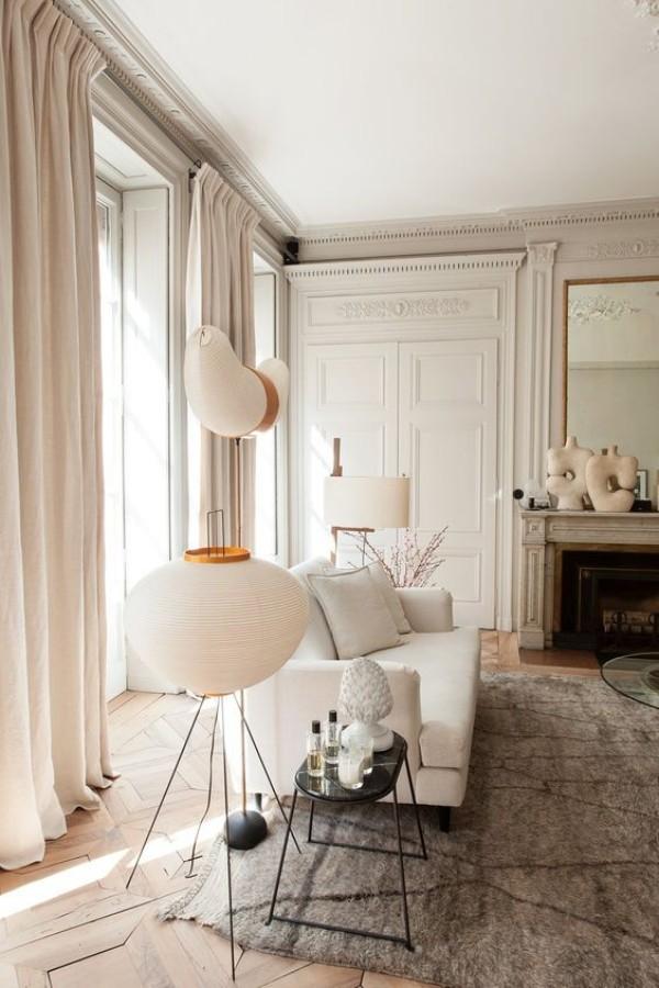 Pariser Chic im Wohnzimmer weiße Wände hellgrauer Teppich weißes Sofa Lampe Kamin Spiegel Deko Artikel