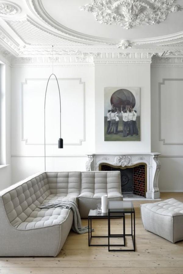 Pariser Chic im Wohnzimmer weißes Interieur Stehlampe Ecksofa verzierte Decke Rosette Bild Kamin