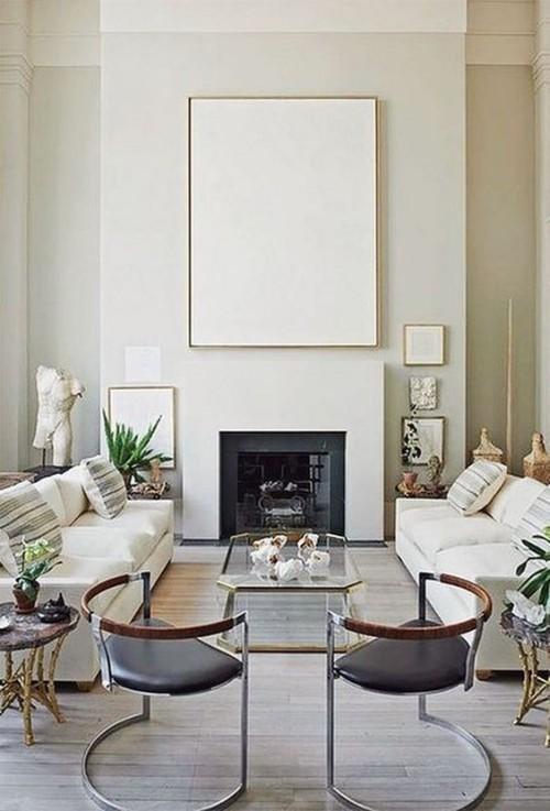 Asymmetrie im Interieur Wandbilder Skulpturen um den Kamin durchbrechen das symmetrische Raumdesign schön eingerichtetes Wohnzimmer