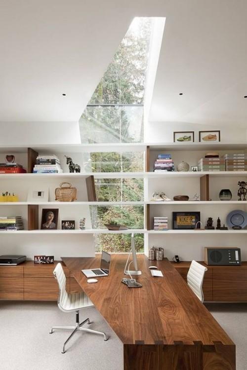 Asymmetrie im Interieur asymmetrisches Dachfenster Bücherregale langer Holztisch zwei Stühle