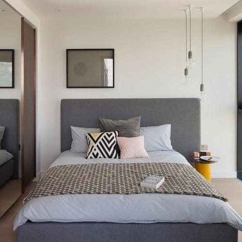 Asymmetrie im Interieur grau gestaltetes Schlafzimmer hängende Elektrobirnen recht Wandspiegel links Schlafbett