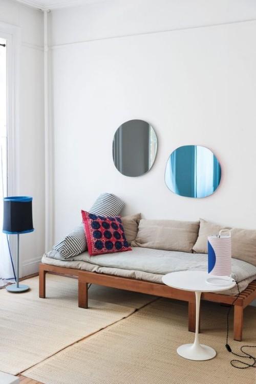 Asymmetrie im Interieur schlicht eingerichtetes Wohnzimmer zwei runde Spiegel an der Wand über dem Sofa Kissen Stehlampe