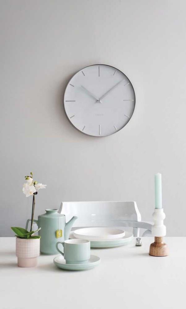 Eine weiße Wanduhr mit Geschirr auf dem Tisch