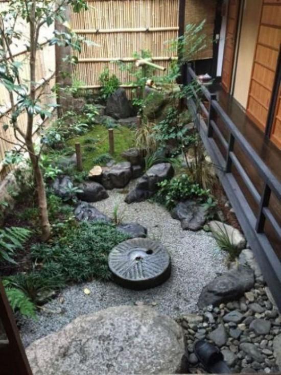 Japanischer Garten im Hinterhof Bambuswand Steine Moos Kies grüne Pflanzen niedriger Zaun