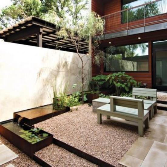 Japanischer Garten im Hinterhof Ort der Ruhe Wasser Kies grüne Pflanzen Sitzbänke