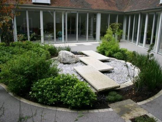 Japanischer Garten im Hinterhof runde Form Steinplatten Felsbrocken Kiesel grüne Sträucher