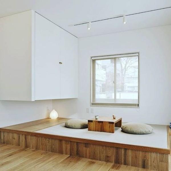 Japanisches Wohnzimmer reduzierte Ästhetik niedriger Tisch zwei Bodenkissen weiße Wände