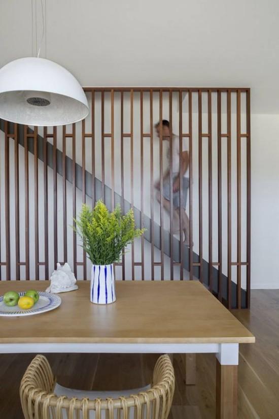 Raumteiler aus Holz Lattenrost versteckt diskret die Treppe zum zweiten Stock abgesondert vom dem Esszimmer