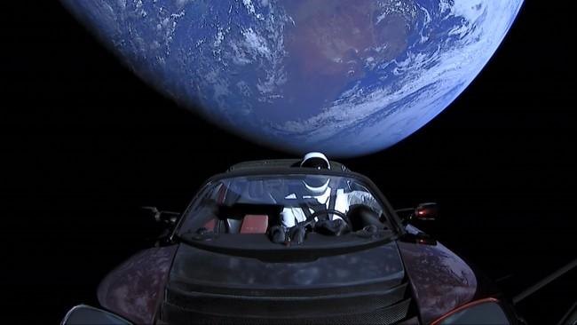 Starman auf dem Tesla Roadster kreist zum ersten Mal um die Sonne die erde im hintergrund