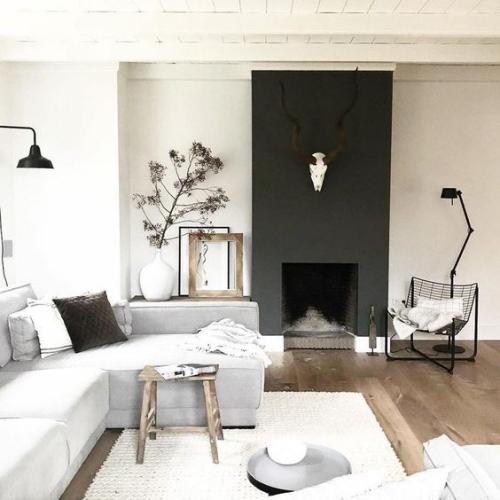 Wohnzimmer in Schwarz-Weiß Holzboden weitere Holzelemente Stuhl Bilderrahmen