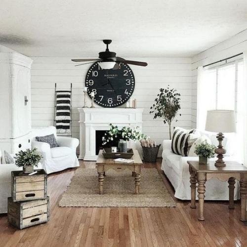 Wohnzimmer in Schwarz-Weiß Vintage Holzkisten zwei Holztische große schwarze Wanduhr viele Blumen
