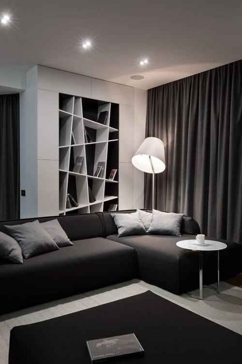Wohnzimmer in Schwarz-Weiß Zwischentöne Graunuancen dunkles Interieur Lampe Regal Vorhänge Beistelltisch