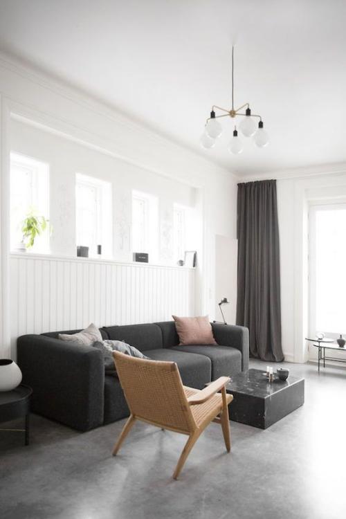Wohnzimmer in Schwarz-Weiß beigefarbener Stuhl Kissen hohe Fenster grauer Boden Industrial Style Touches